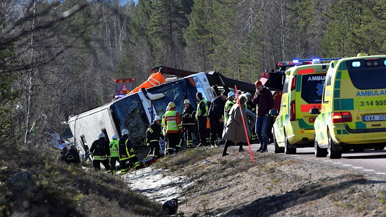 Räddningspersonal arbetar runt en buss som kört av vägen