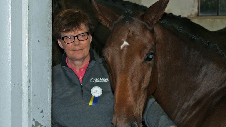 Aja Blomberg Andersson står bredvid en brun häst, som har ett vitt tecken i pannan.