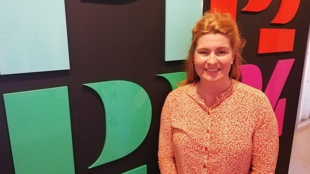 En kvinna står framför Sveriges Radios logga