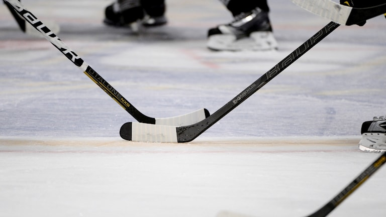 Två hockeyklubbor redo för tekning.