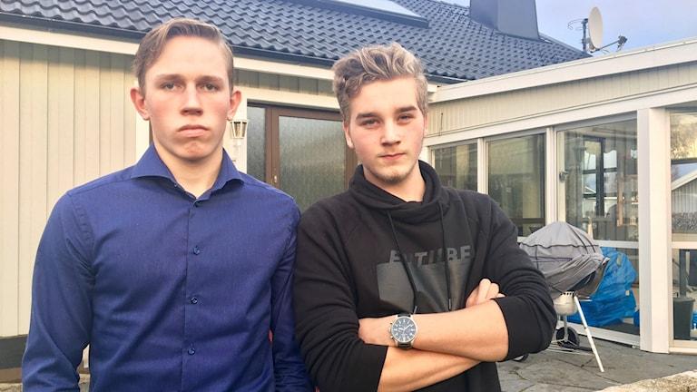 Två ungdomar iklädd blå skjorta och svart hoodie står framför ett ljusgult hus.