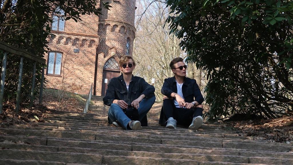 Två killar sitter utomhus på en trappa.