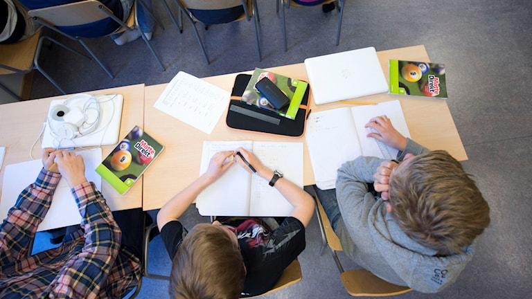 Tre elever vid skolbänkar i ett klassrum. Foto: Fredrik Sandberg/TT.