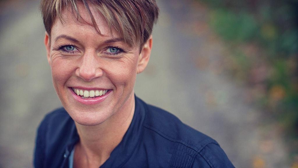 Porträttbild på en kvinna i utomhusmiljö. I bakgrunden skymtas en grusväg.