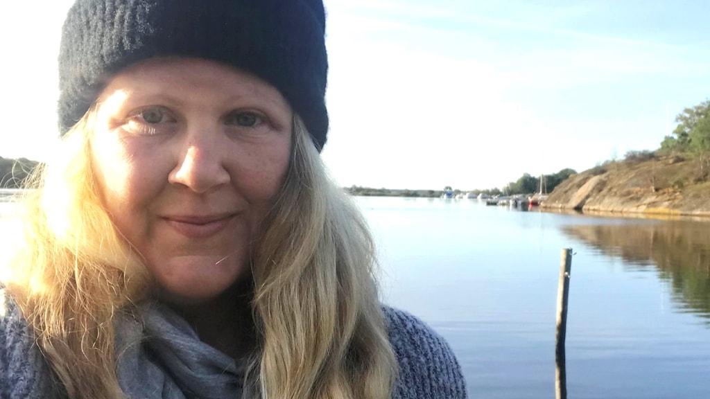 Närbild på medelålderskvinna i mössa vid en sjö.