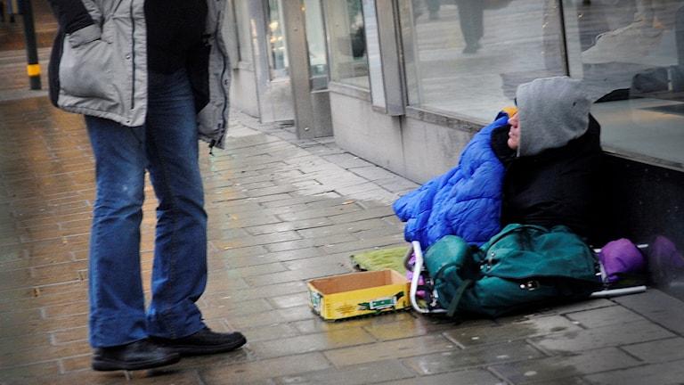 En hemlös person sitter i en sovsäck vid ett skyltfönster. En annan person har stannat bredvid för att skänka pengar. Foto: Hasse Holmberg/TT.