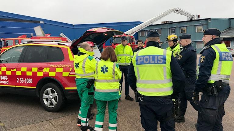 Polis och ambulanspersonal framför en industribyggnad där en eld släcks.