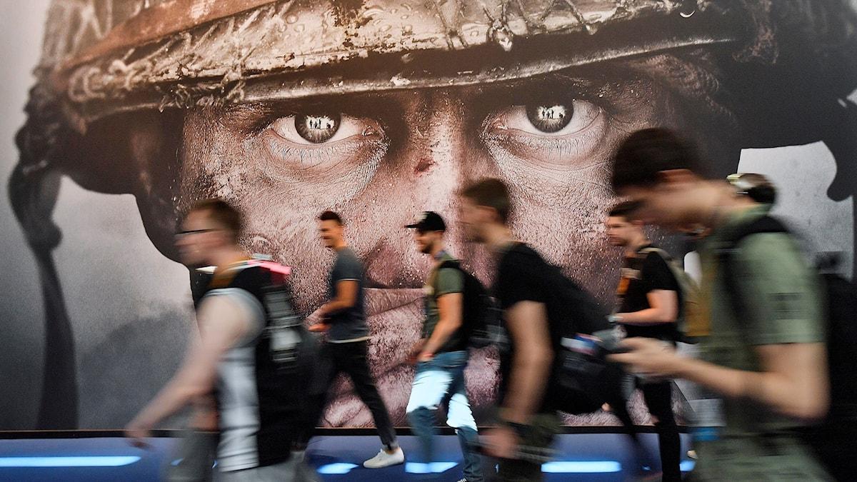 Besökare passerar en affisch på den stora spelmässan Gamescom i augusti 2017.