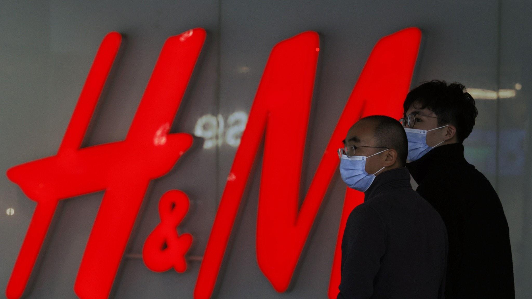 Personer med munskydd framför H&M butik