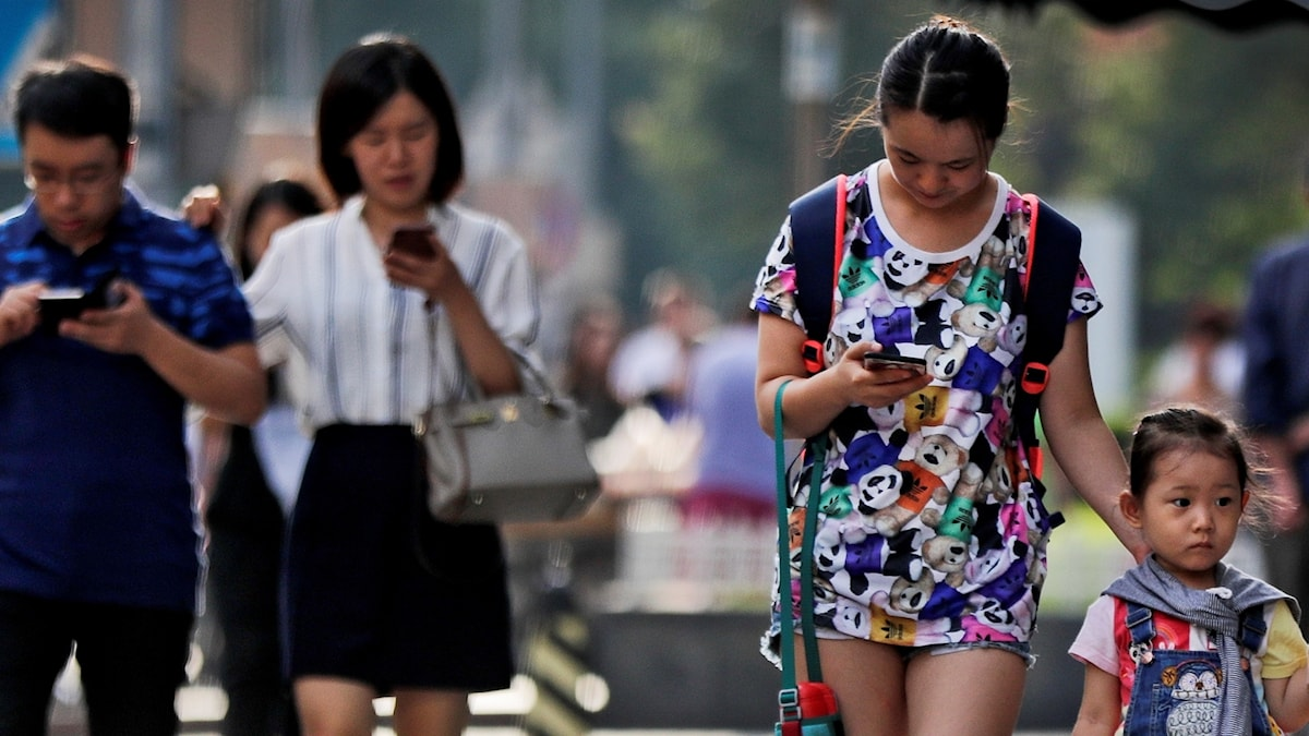 Människor på gatan tittar ned på sina mobilskärmar.