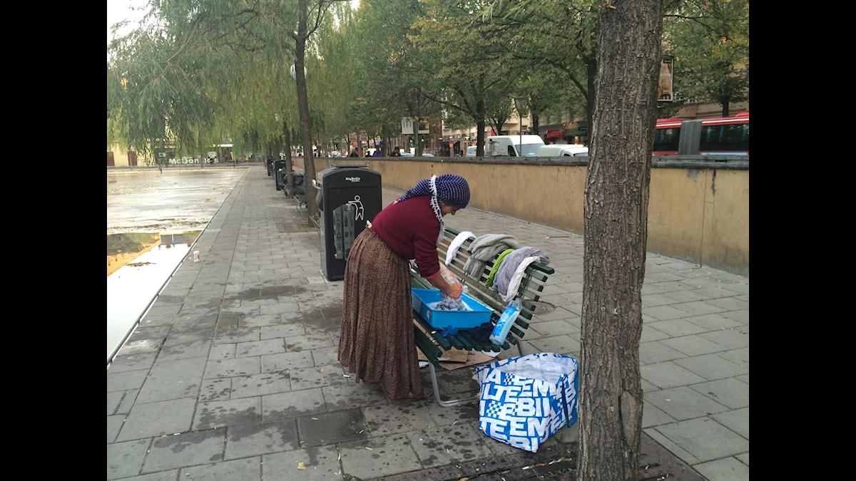 Kvinna tvättar kläder på Sveavägen