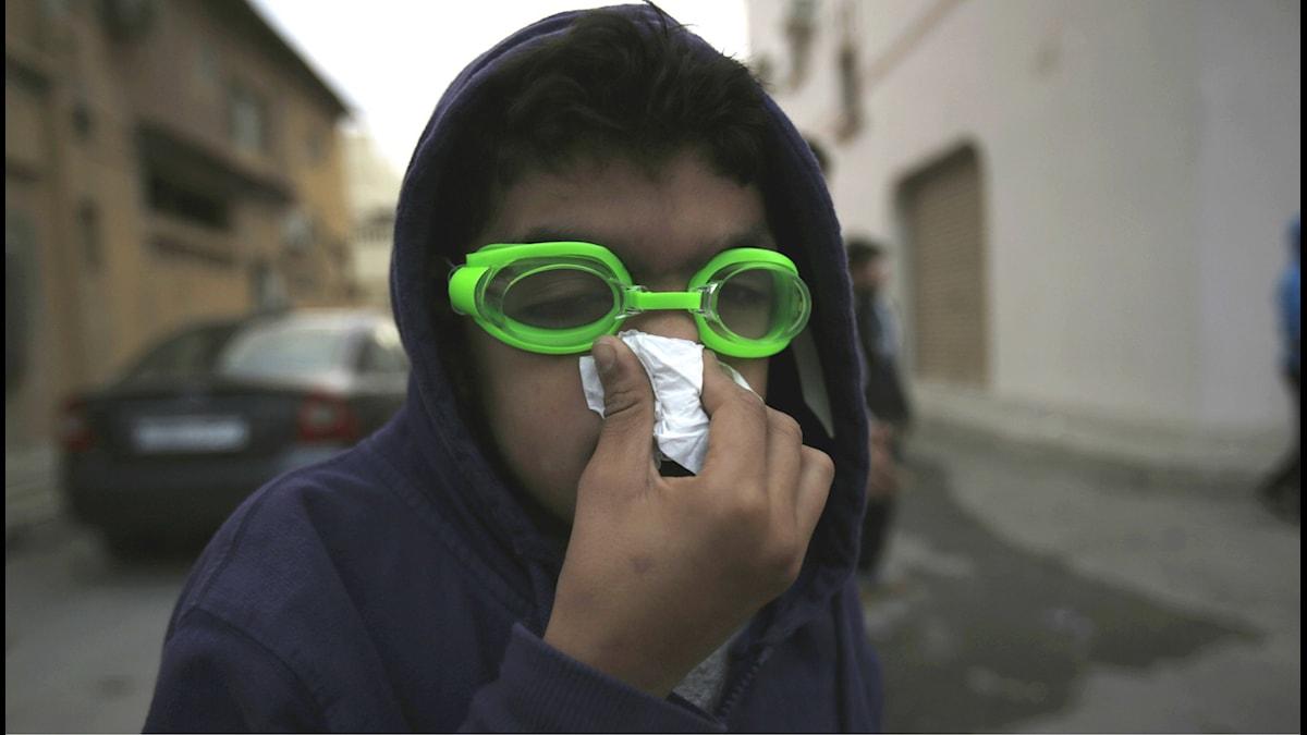En ung pojke skyddar sig mot tårgas under protester i Bahrain, mot Saudiarabiens avrättning av shialedaren Nimr al-Nimr i januari. Bahrain är en av många platser i Mellanöstern där konflikten mellan Saudiarabien och Iran ställts på sin spets. Foto: Hasan Jamali/TT