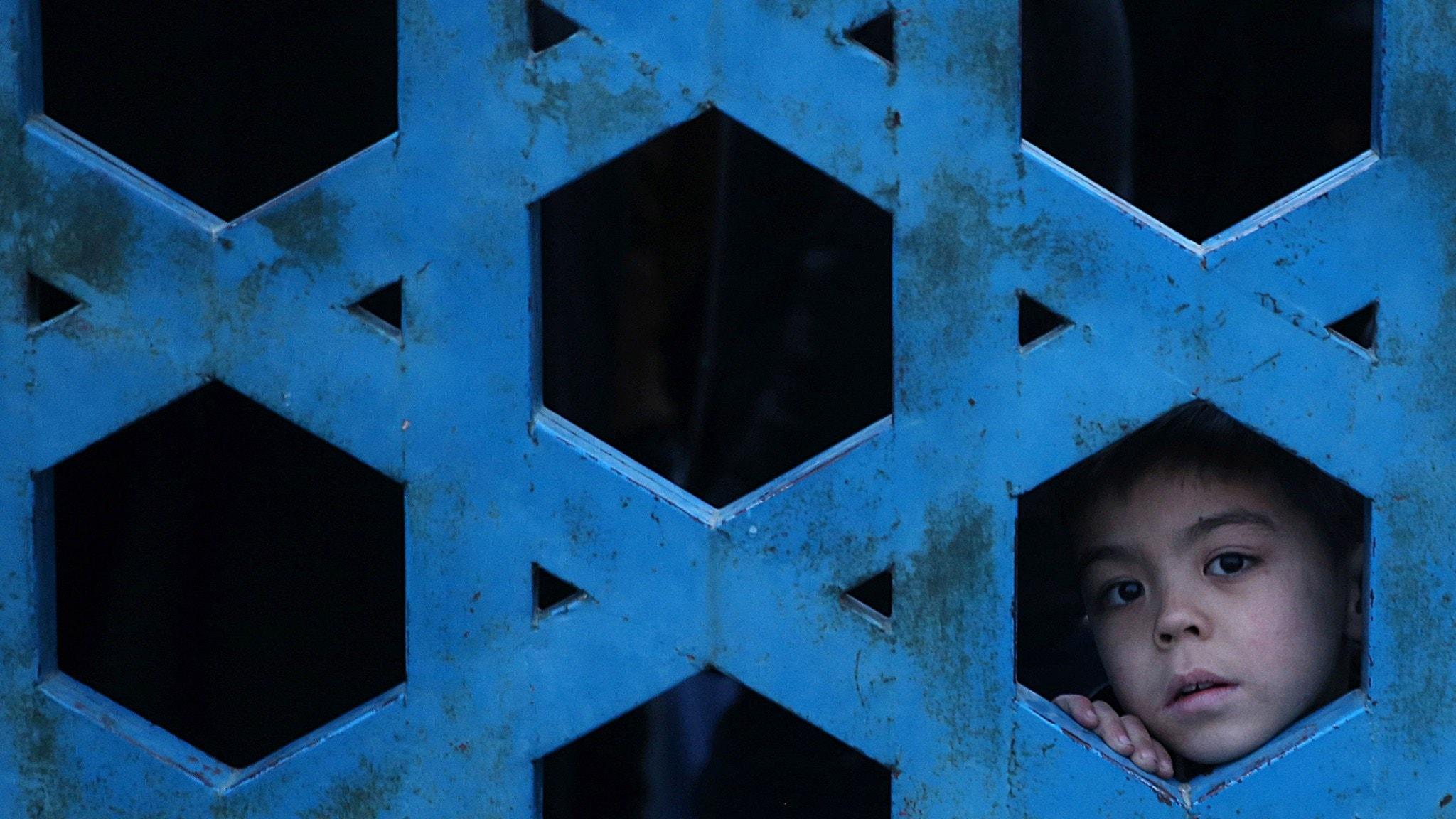 En hazarpojke tittar på en minnesceremoni för halshuggna hazarer i Afghanistan.