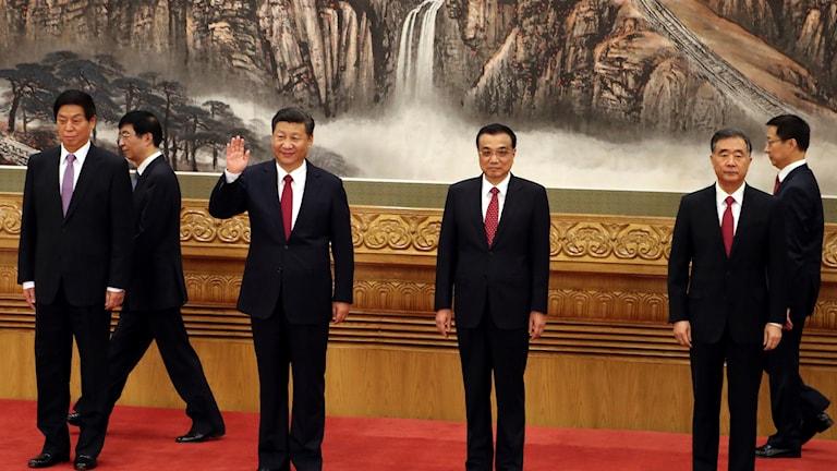 """Kinas president Xi Jinping vinkar mot världen. I bakgrunden till vänster mannen som beskrivs som hjärnan bakom den """"kinesiska drömmen"""", Wang Huning."""