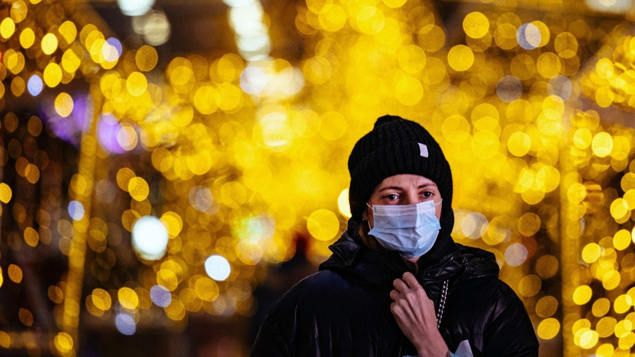 Kvinna i ansiktsmask i ett julpyntat Moskva.