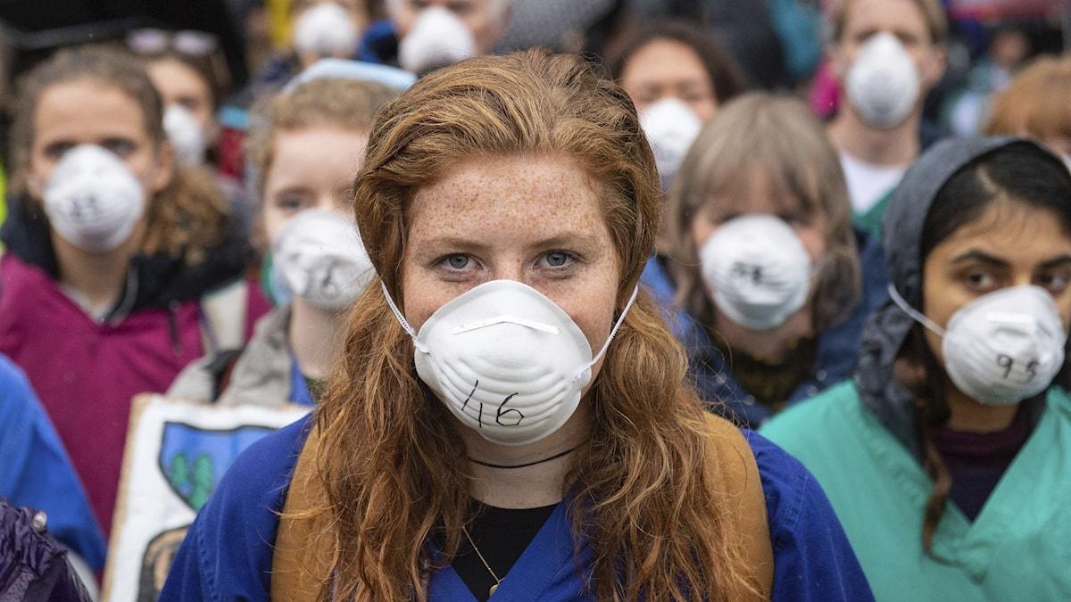 En rödhårig kvinnlig läkare står längst fram i en folkmassa där alla bär kirurgmasker.