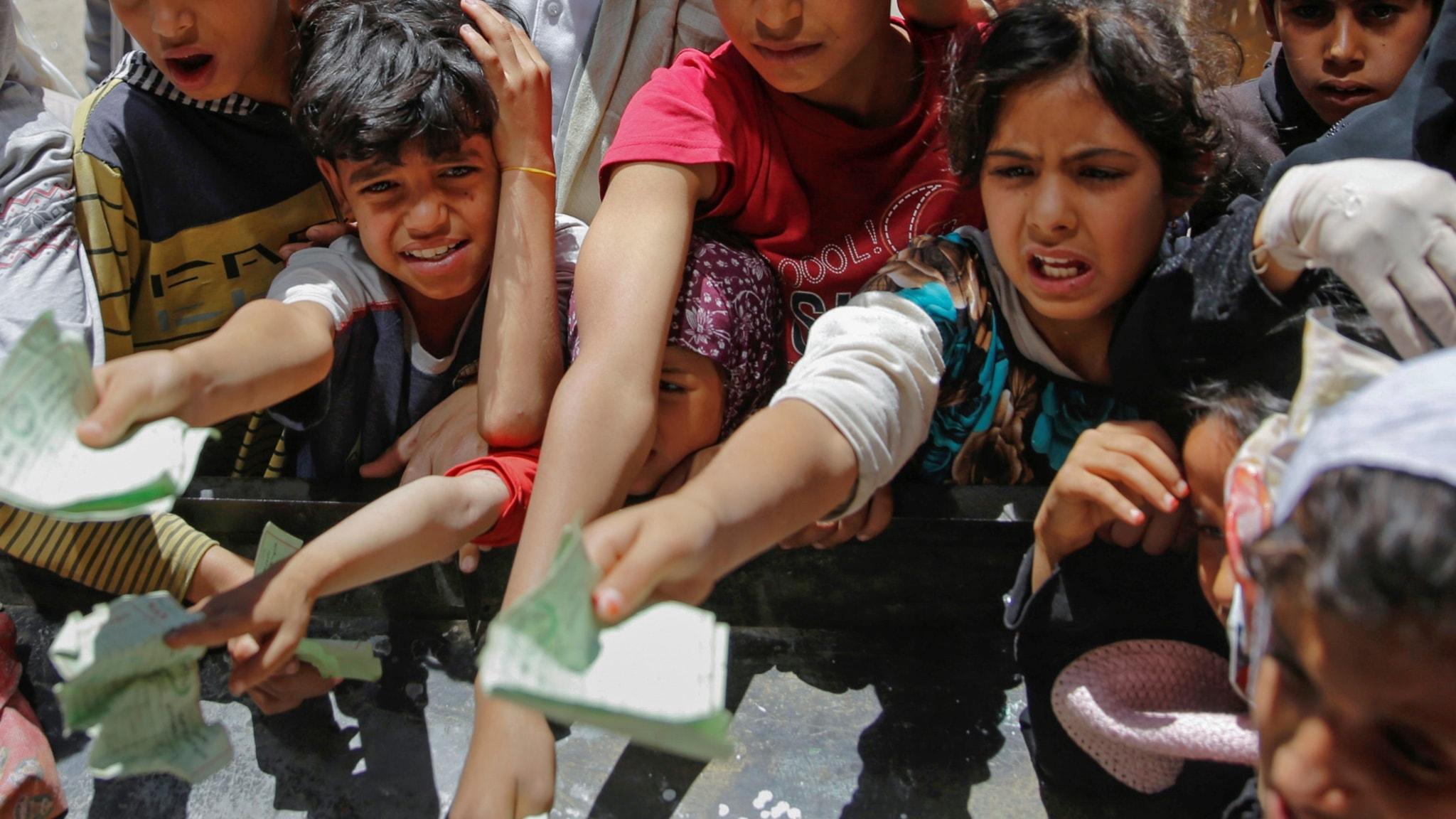 Vuxna och barn använder kuponger för att få hämta ut matransoner