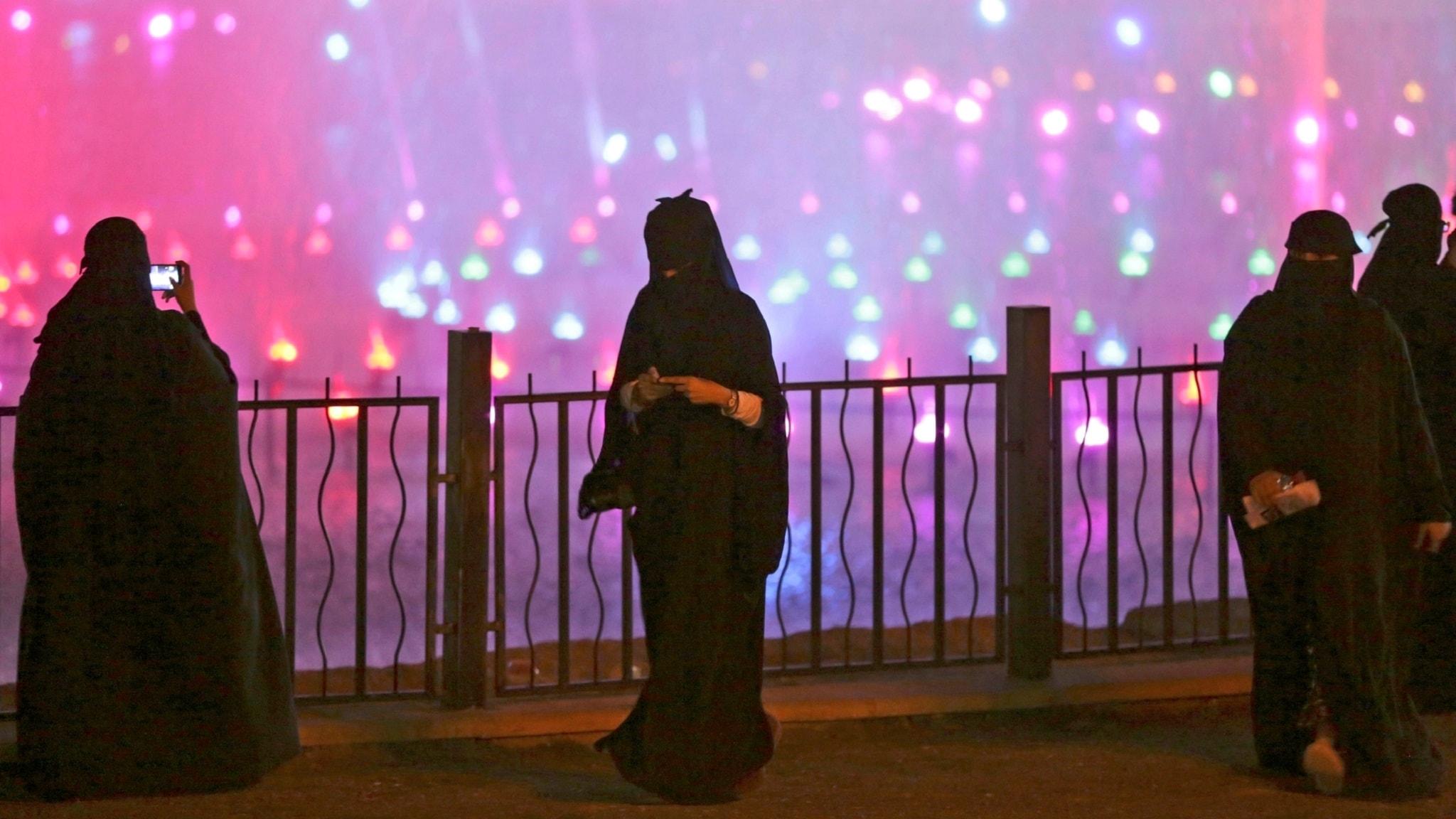 Saudiska kvinnor klädda i täckande abayor i Riyadh 2014 fotograferar med sina mobiler.