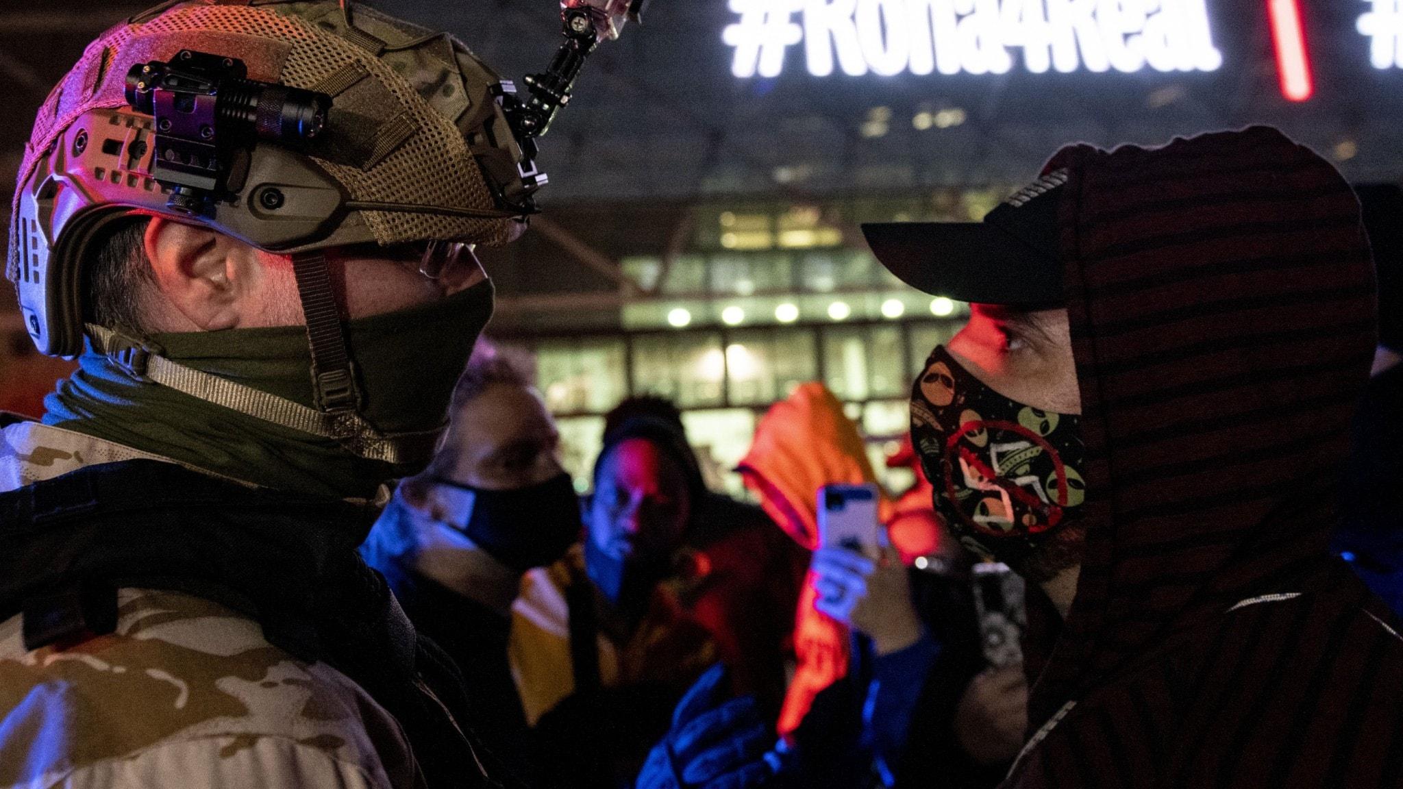 En militärt utrustad Trumpsupporter och en svartklädd motdemonstrant utanför ett rösträkningscenter i Detroit, Michigan.