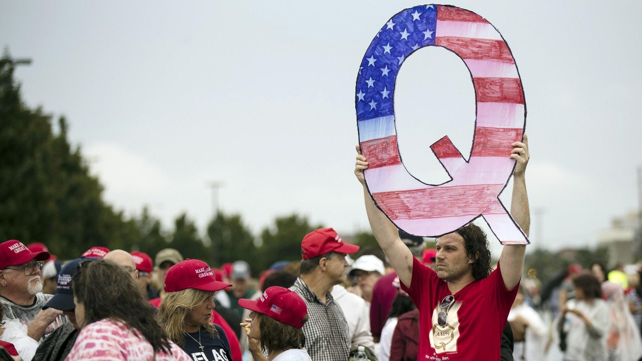 Man håller upp ett Q