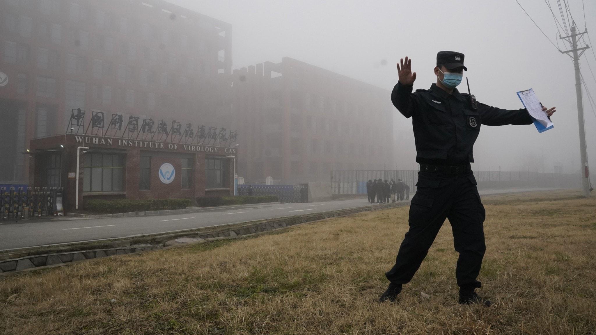 En vakt utanför Wuhans Virusinstitut motar bort journalister under WHO:s besök.