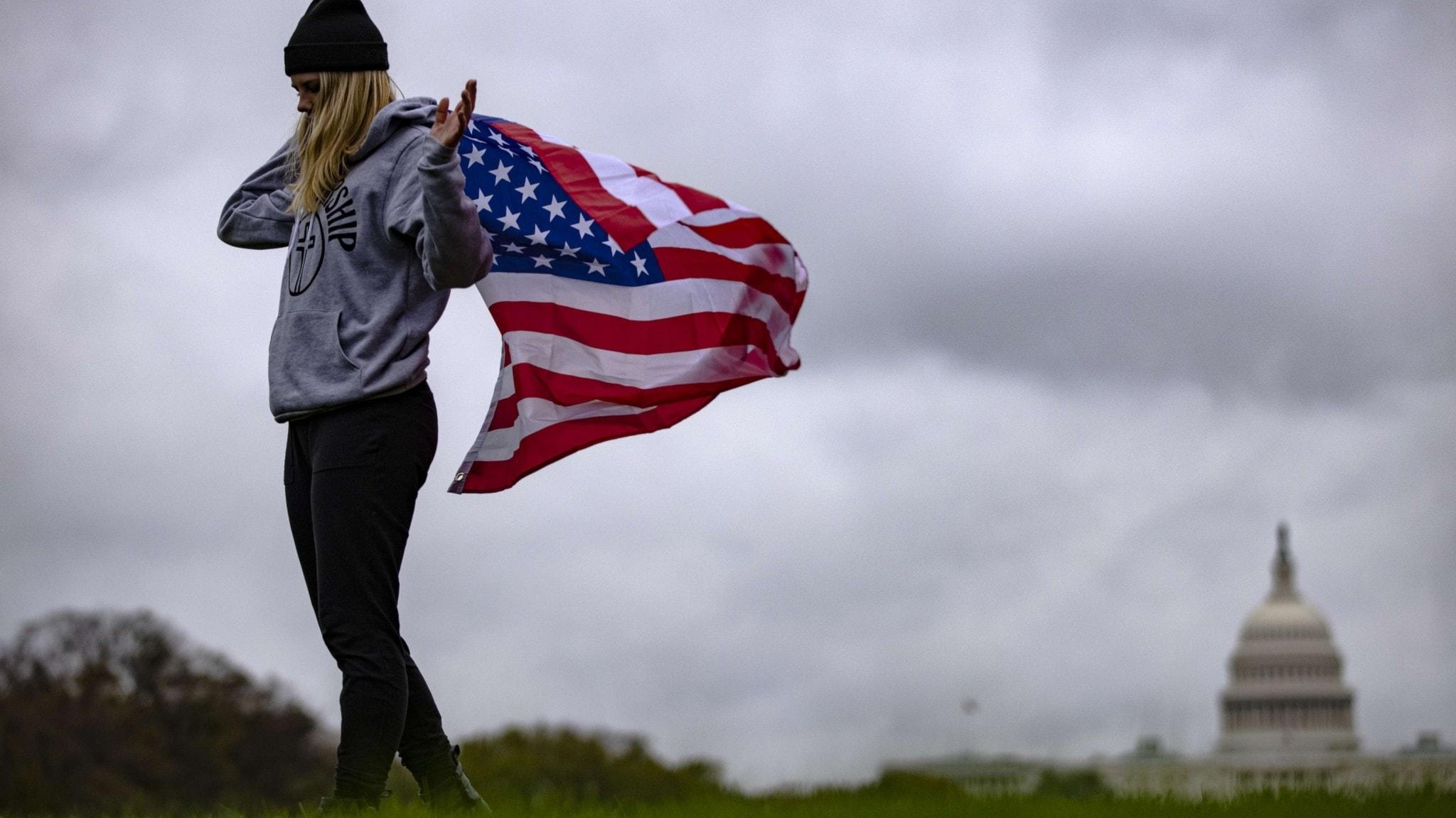 Kvinna med amerikanska flaggan på National Mall i Washington, DC.