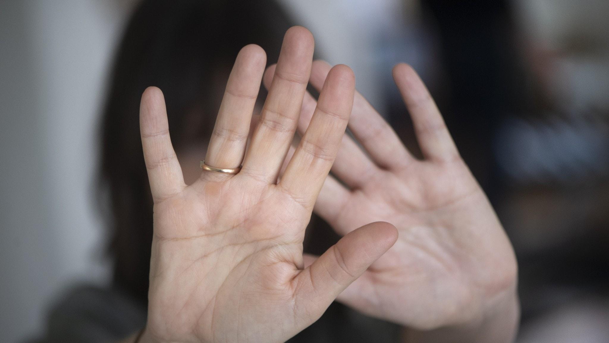 Kvinna skyddar sig med sina händer