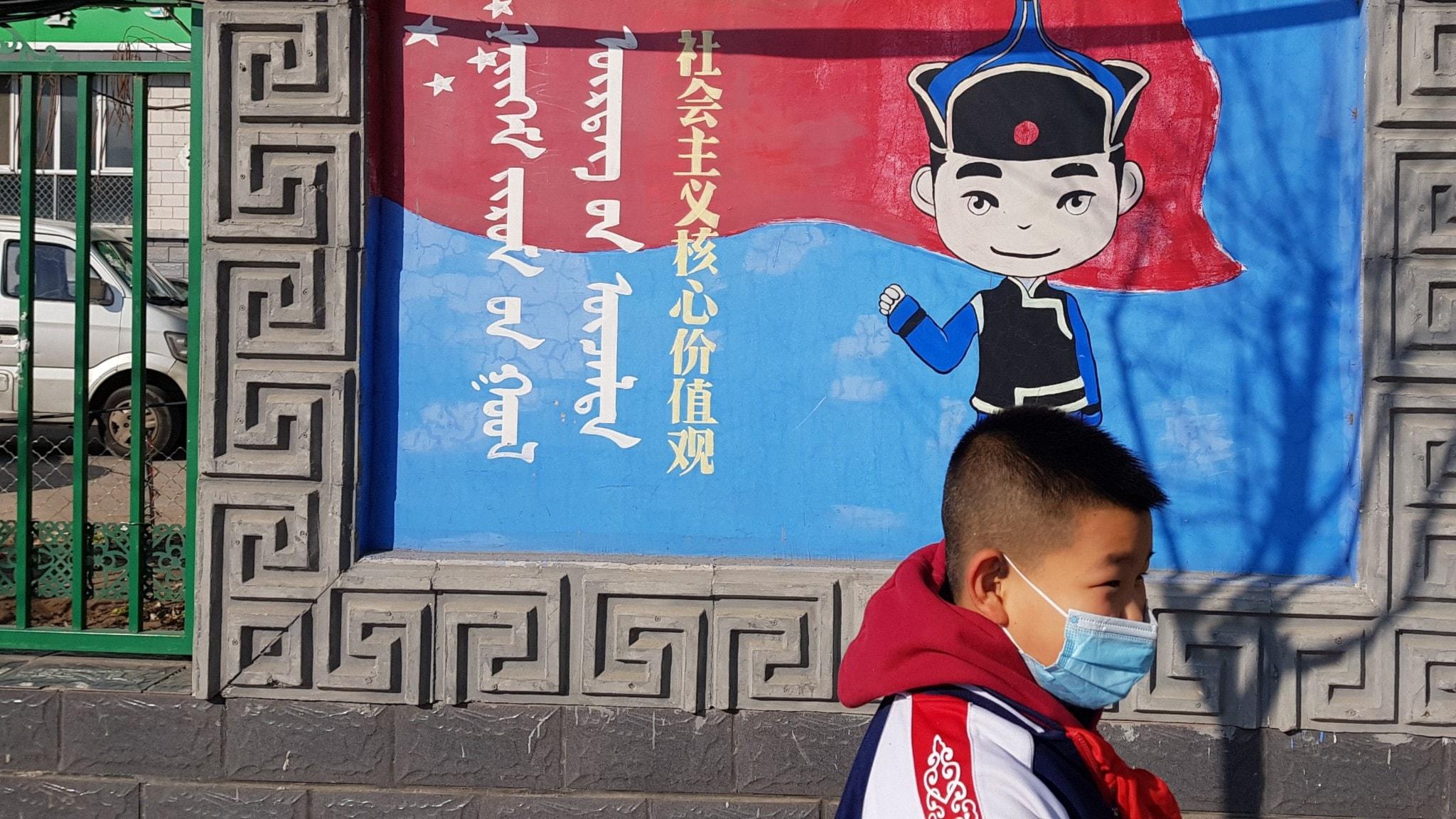 """Pojke i mask utanför skola i Inre Mongoliets huvudstad Hohhot, Kina. På propagandamålningen står """"Socialismens kärnvärderingar""""."""