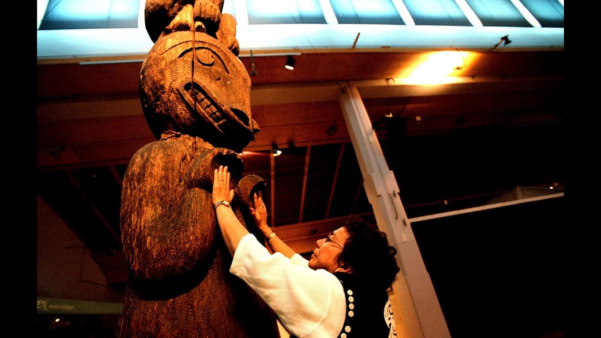 Louisa Smith från Haislaindianerna håller sina händer mot totempålens händer på Etnografiska museet i Stockholm år 2000.