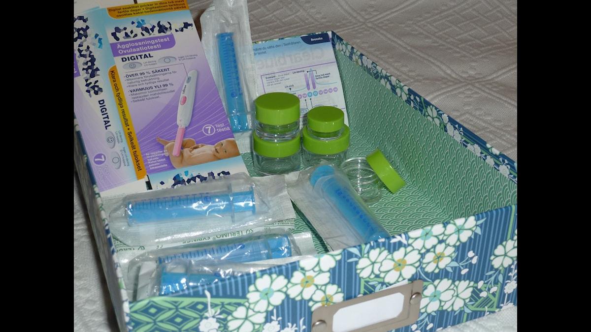 Frida har sparat lådan med sprutor, burkar och ägglossningstest som ett minne av den lyckade spermadonationen.  Foto/montage: Sveriges Radio