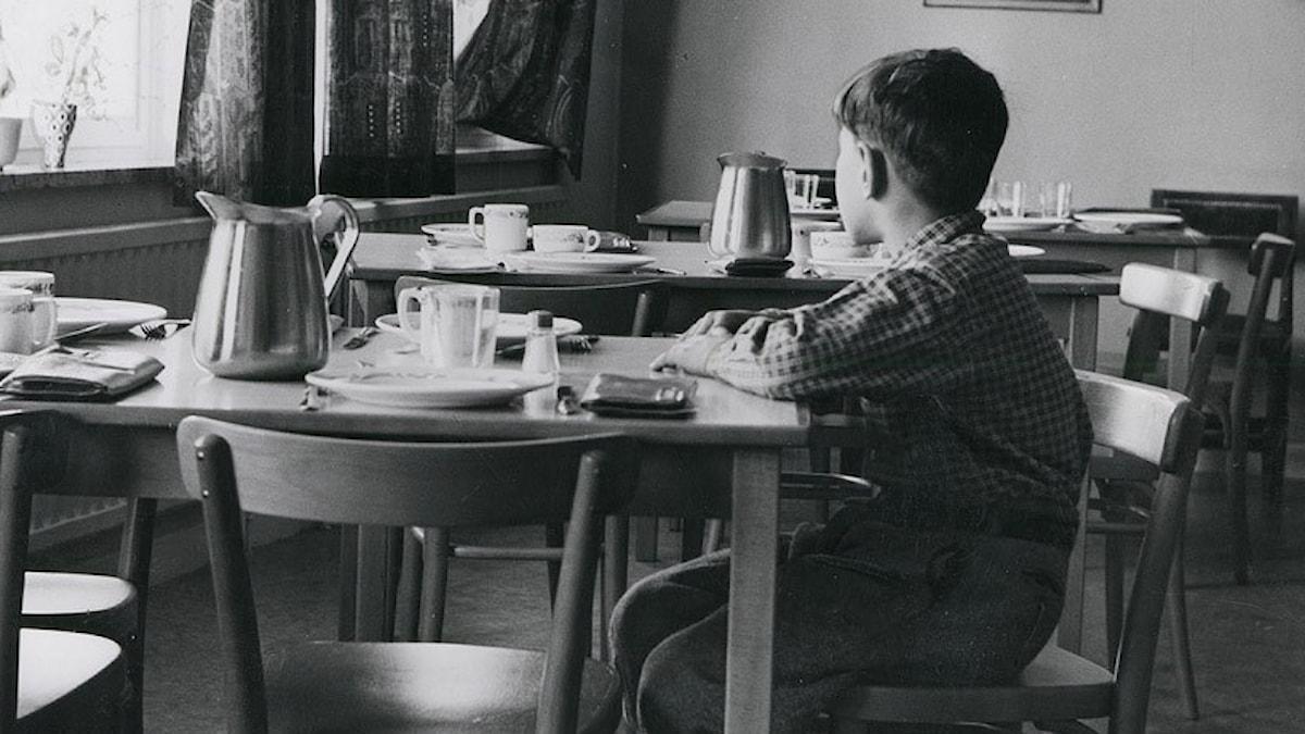 En ensam pojke sitter i matsalen på ett barnhem 1953. Foto: Pressens bild.