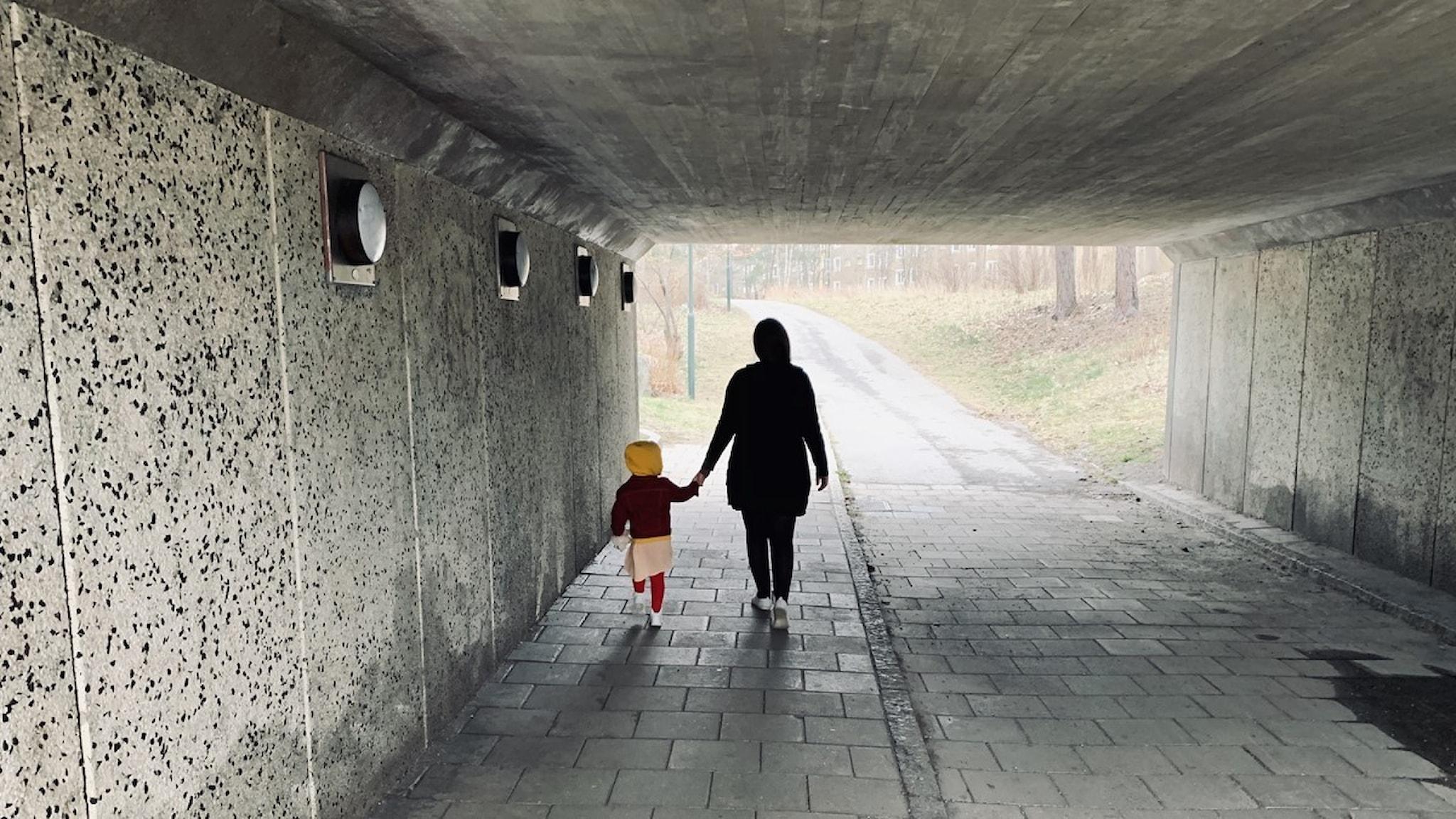 Bild på kvinna och ett barn i gångtunnel