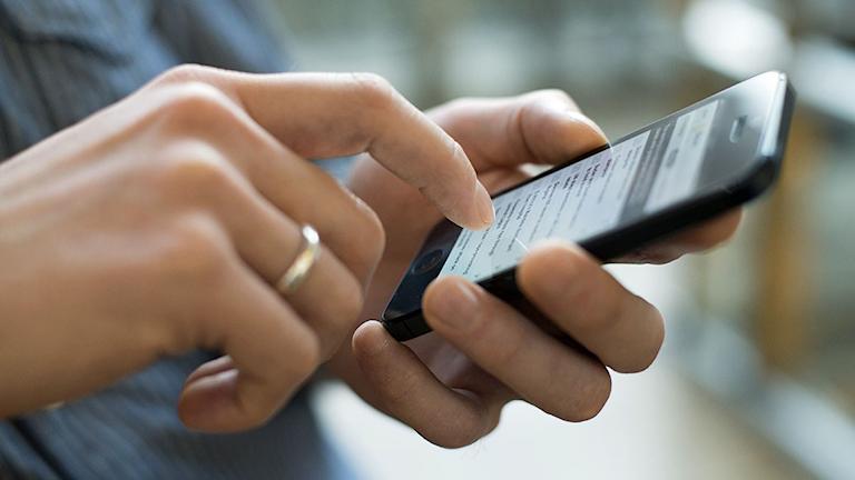 En person skriver på en iphone.