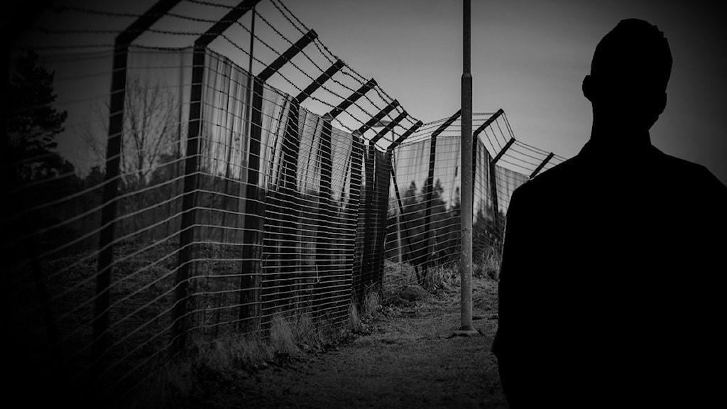 Bild på anonym man framför stängsel.