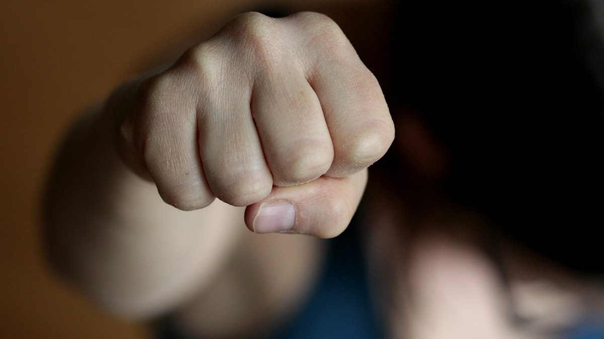 Käsi nyrkissä ja tausta on epätarkka.