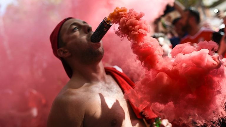 Walesin kannattaja paidatta punainen savusoihtu suussaan.