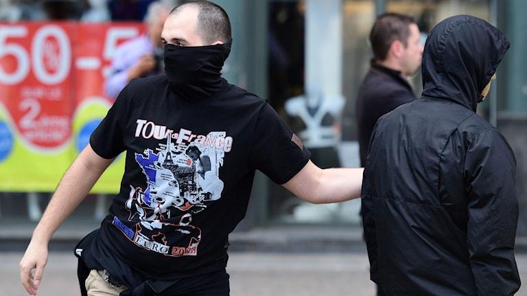 Osittain naamioitunut venäläinen jalkapallofani heittää kiveä kohti Englannin kannattajia.