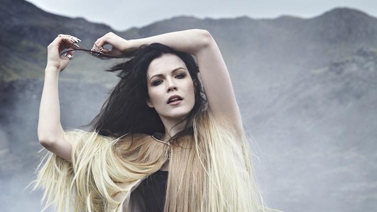 Tummahiuksinen laulaja Jenni Vartiainen, taustalla vuoristoa.