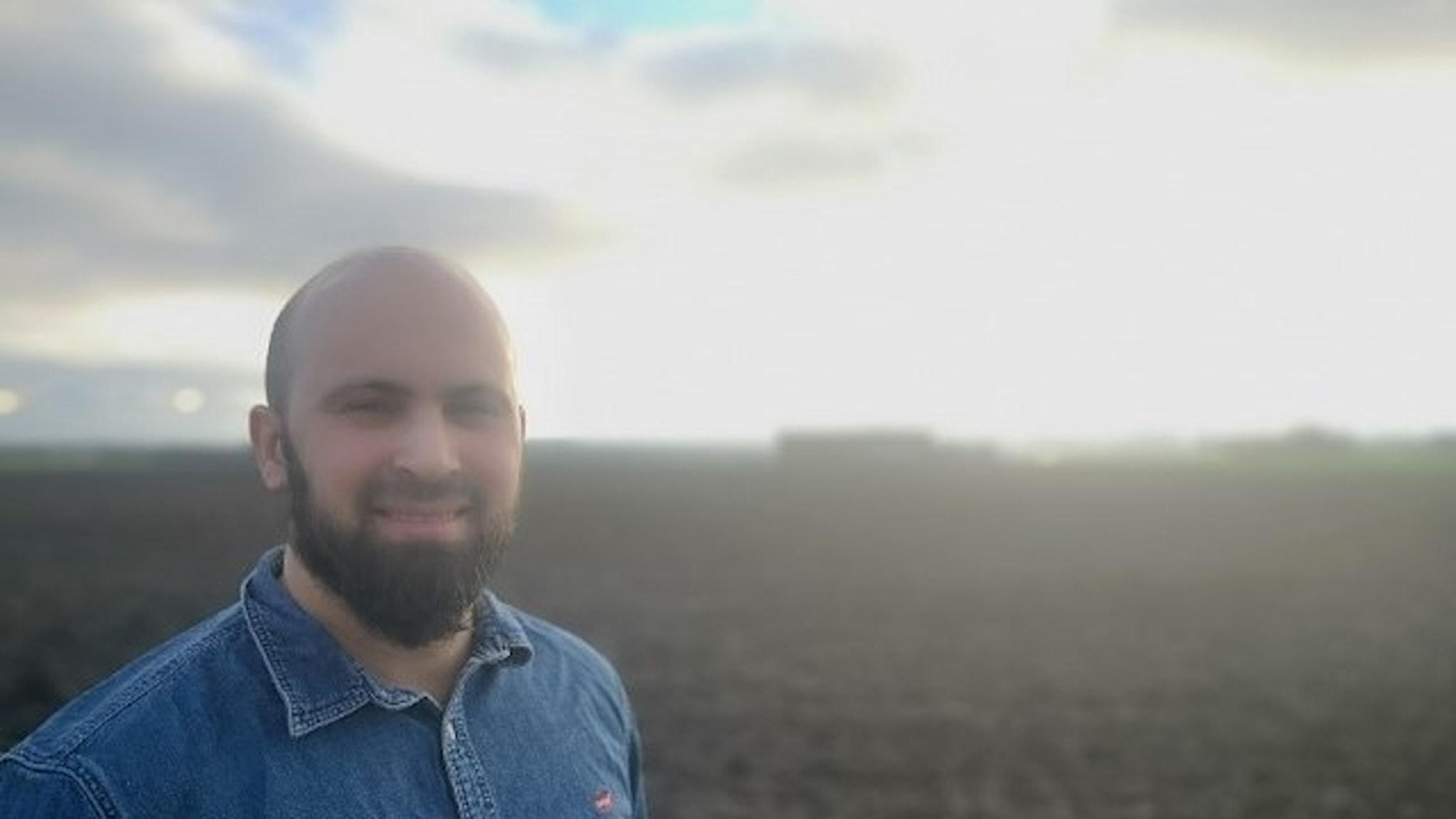 En man med skägg står med mark och himmel bakom sig