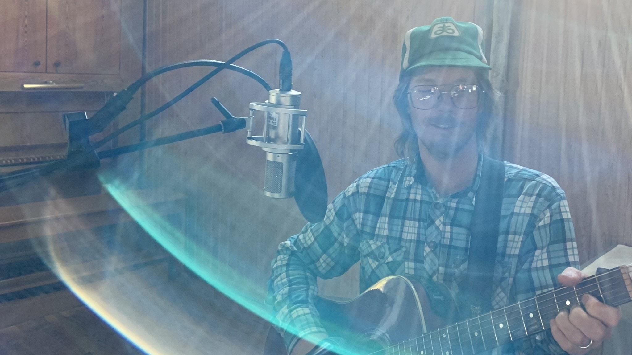 Josh Armfield med mikrofon och gitarr i EFS-kapellet på Sundet utanför Luleå.