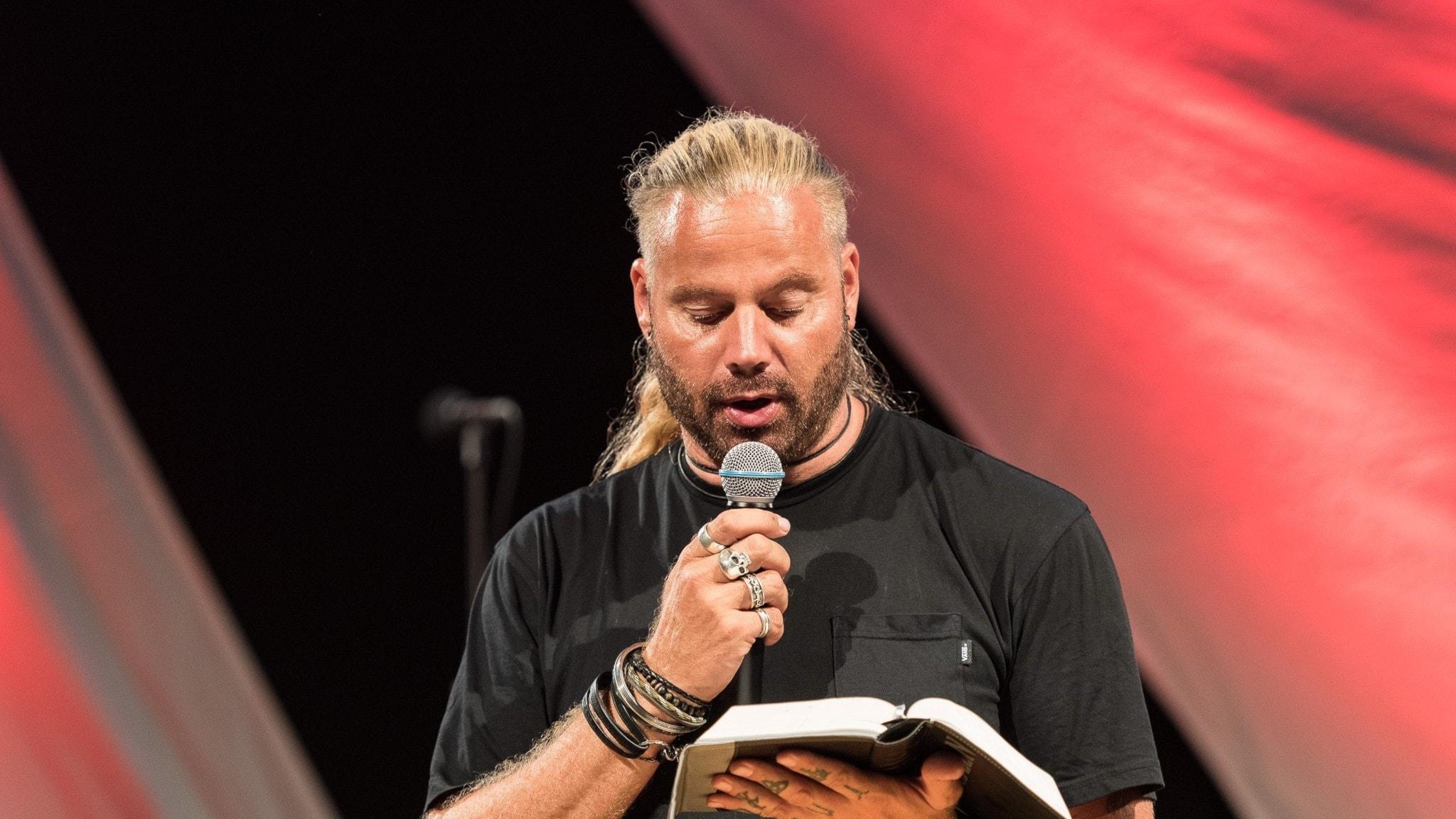 Pastor Marcus Olson läser med en mikrofon på en scen.