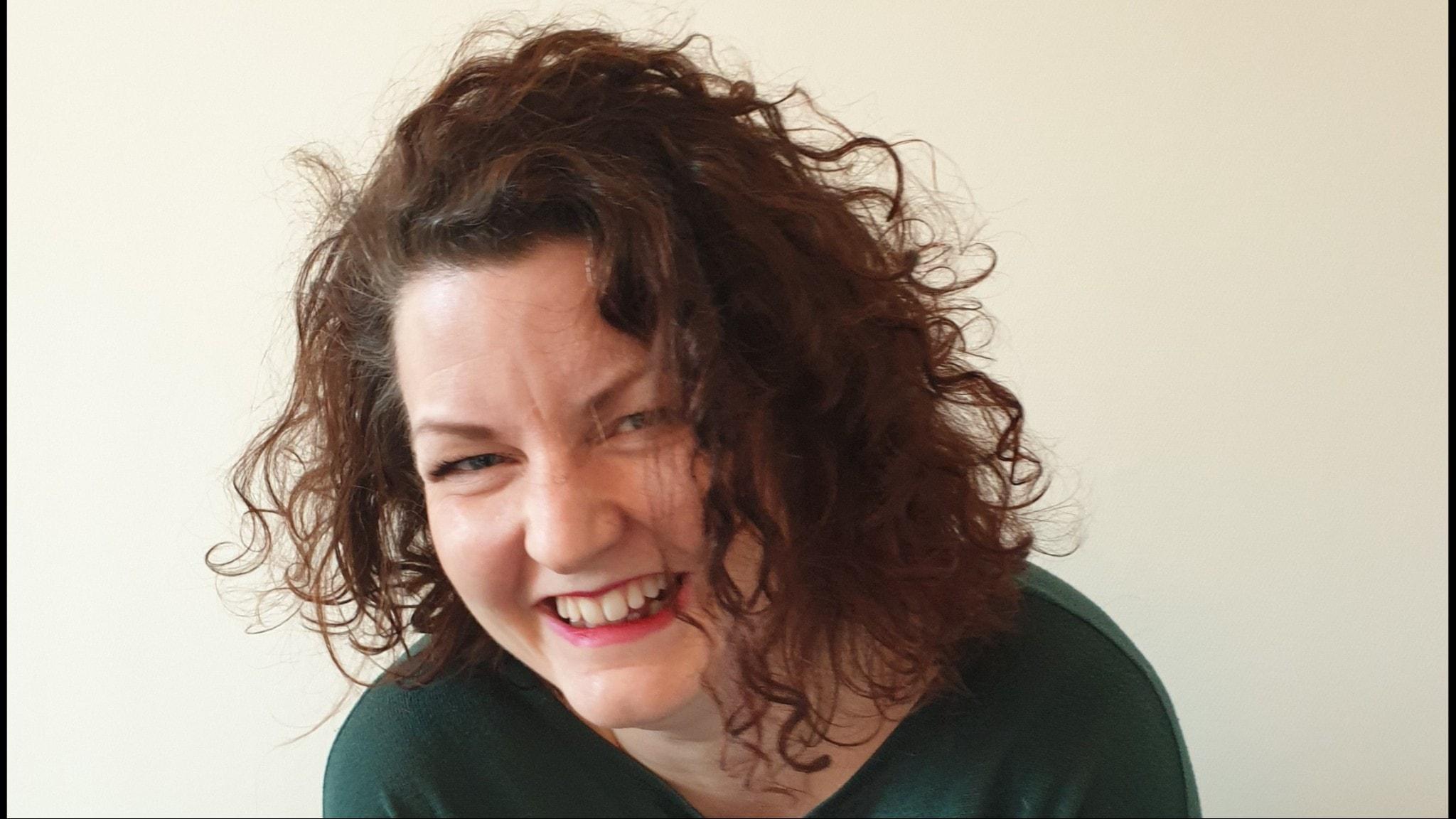 Ung kvinna med mörkt lockigt hår skrattar
