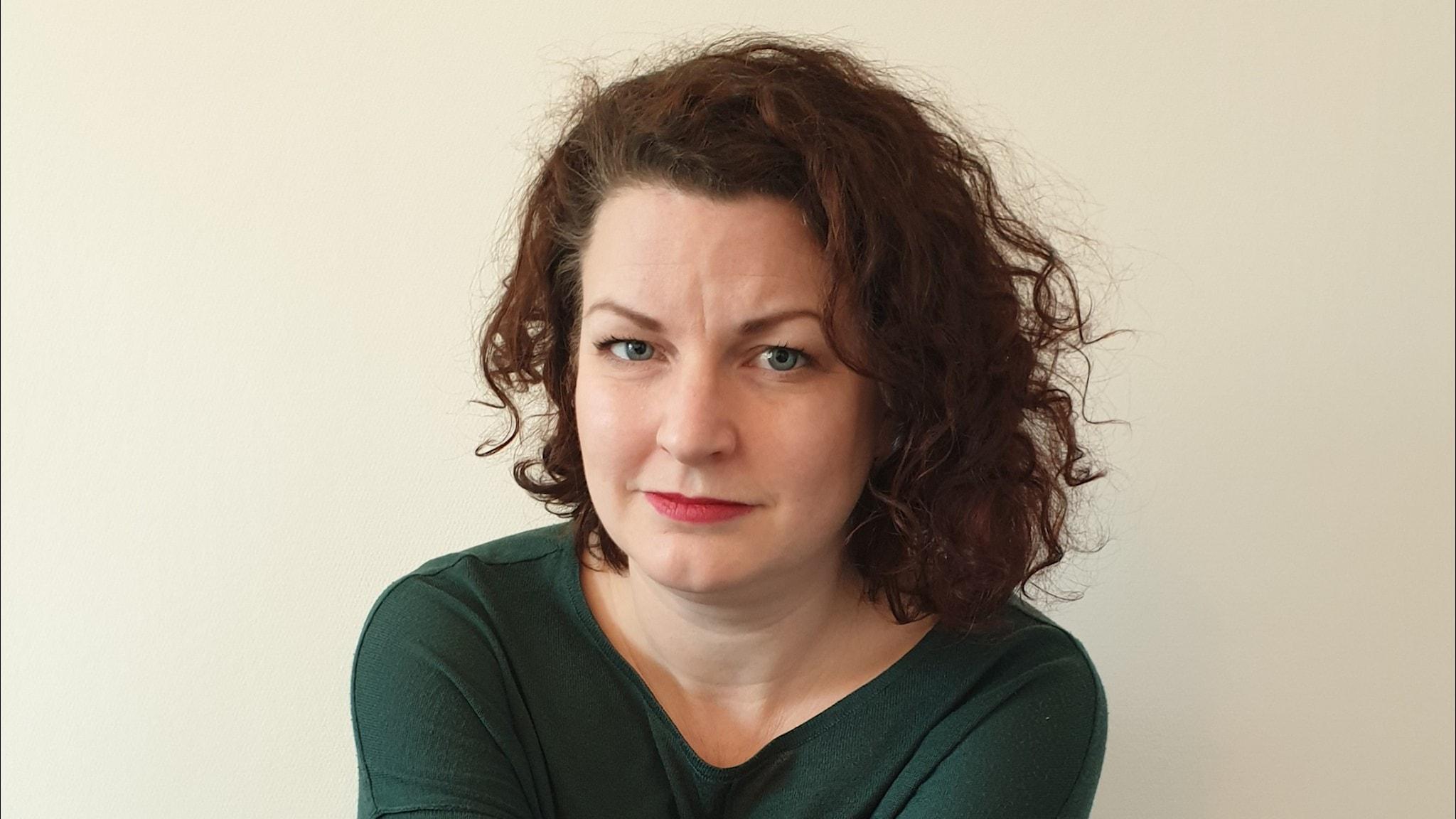 Ung kvinna med mörkt lockigt hår och grön tröja tittar in i kameran
