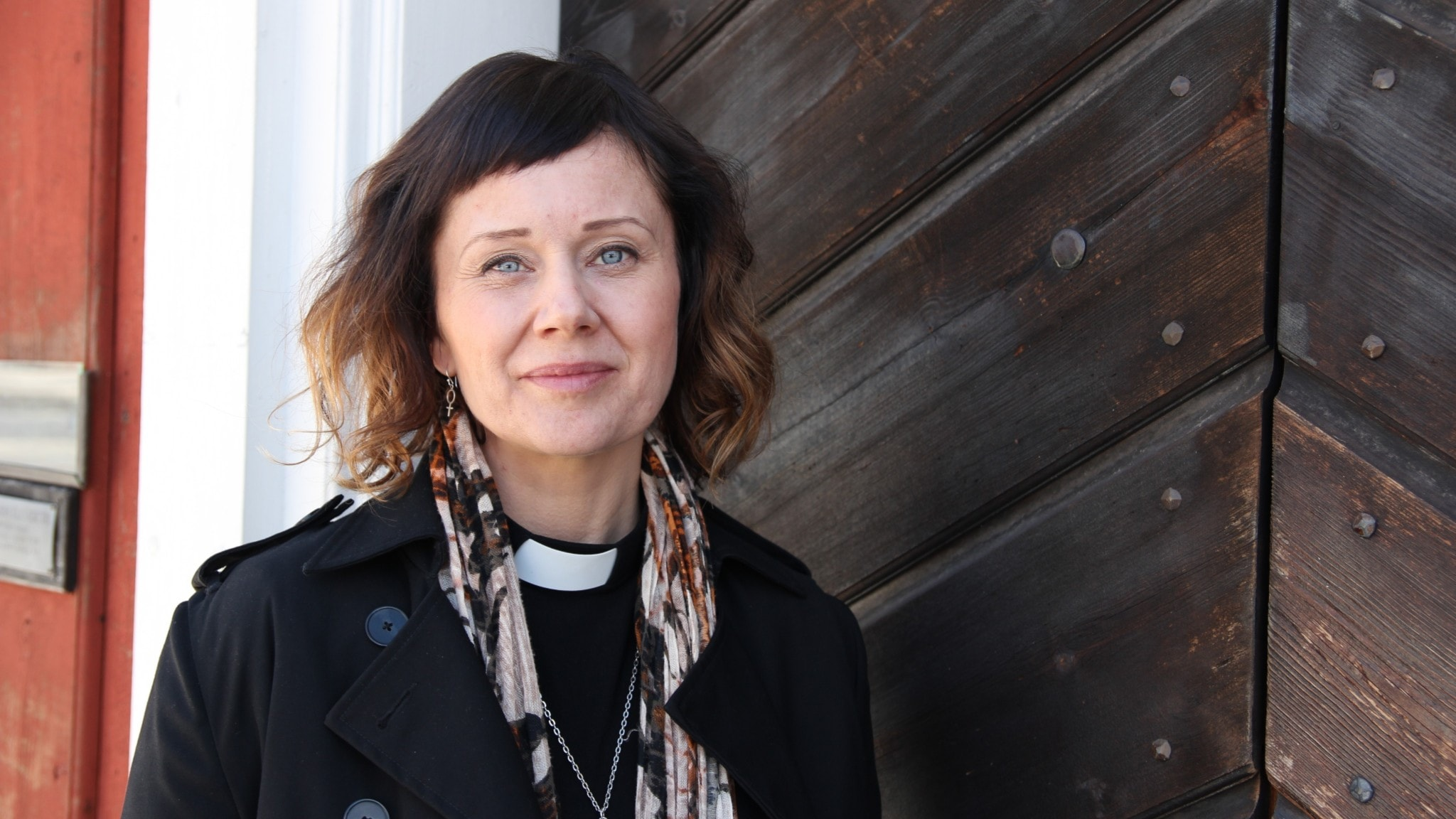 Kvinna i prästskjorta framför en äldre kyrkport i trä.