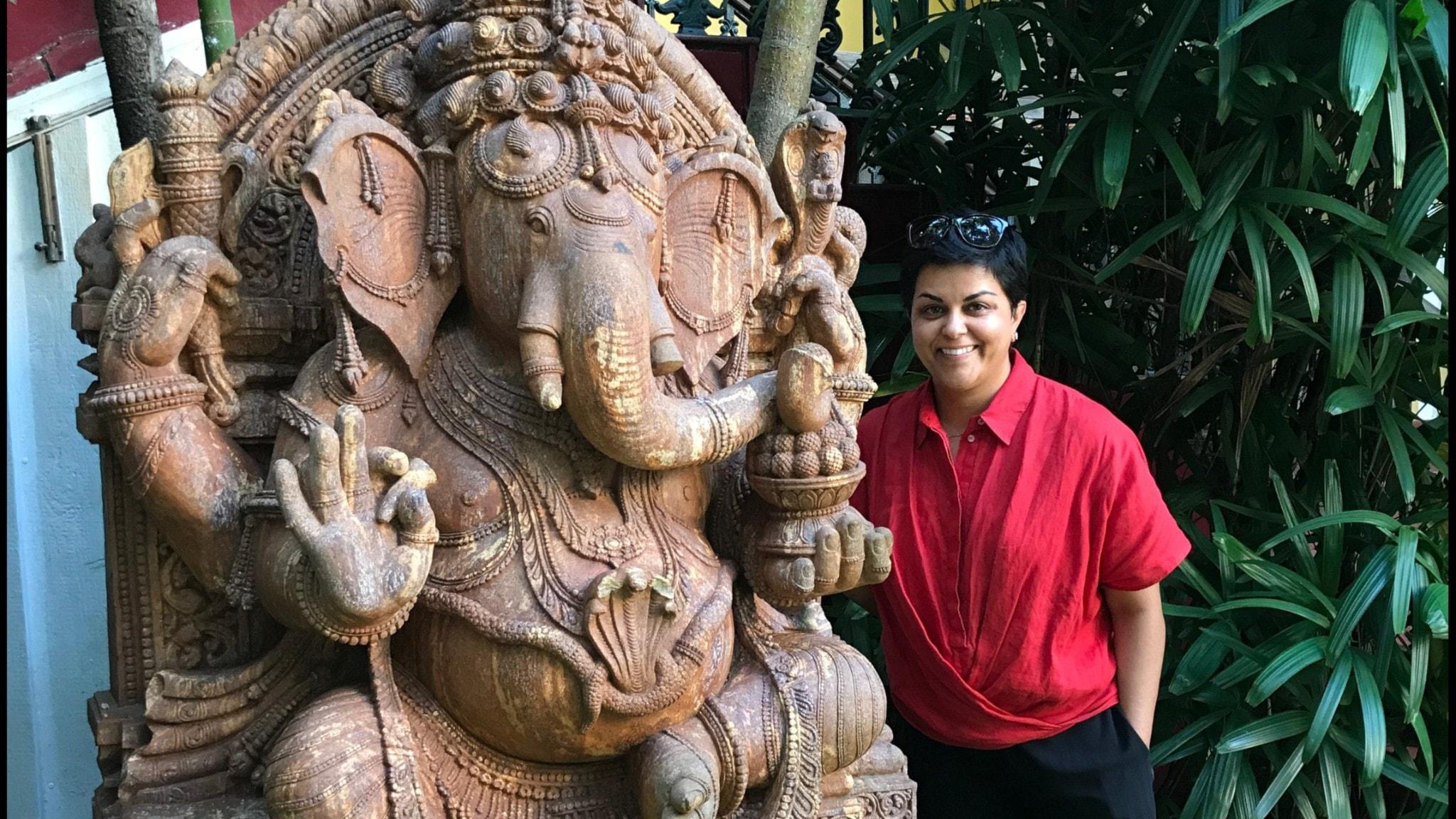 En kvinna i röd tröja står bredvid en Ganesha-staty