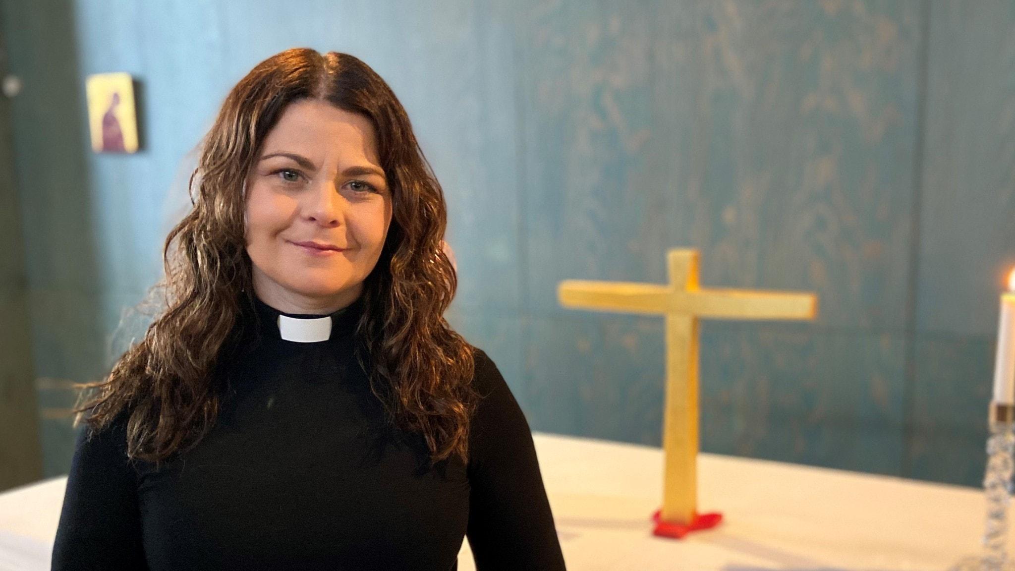 Ida Marcusson i prästskjorta fotograferad med ett guldkors i bakgrunden. Fotot är taget i Porsökyrkan.