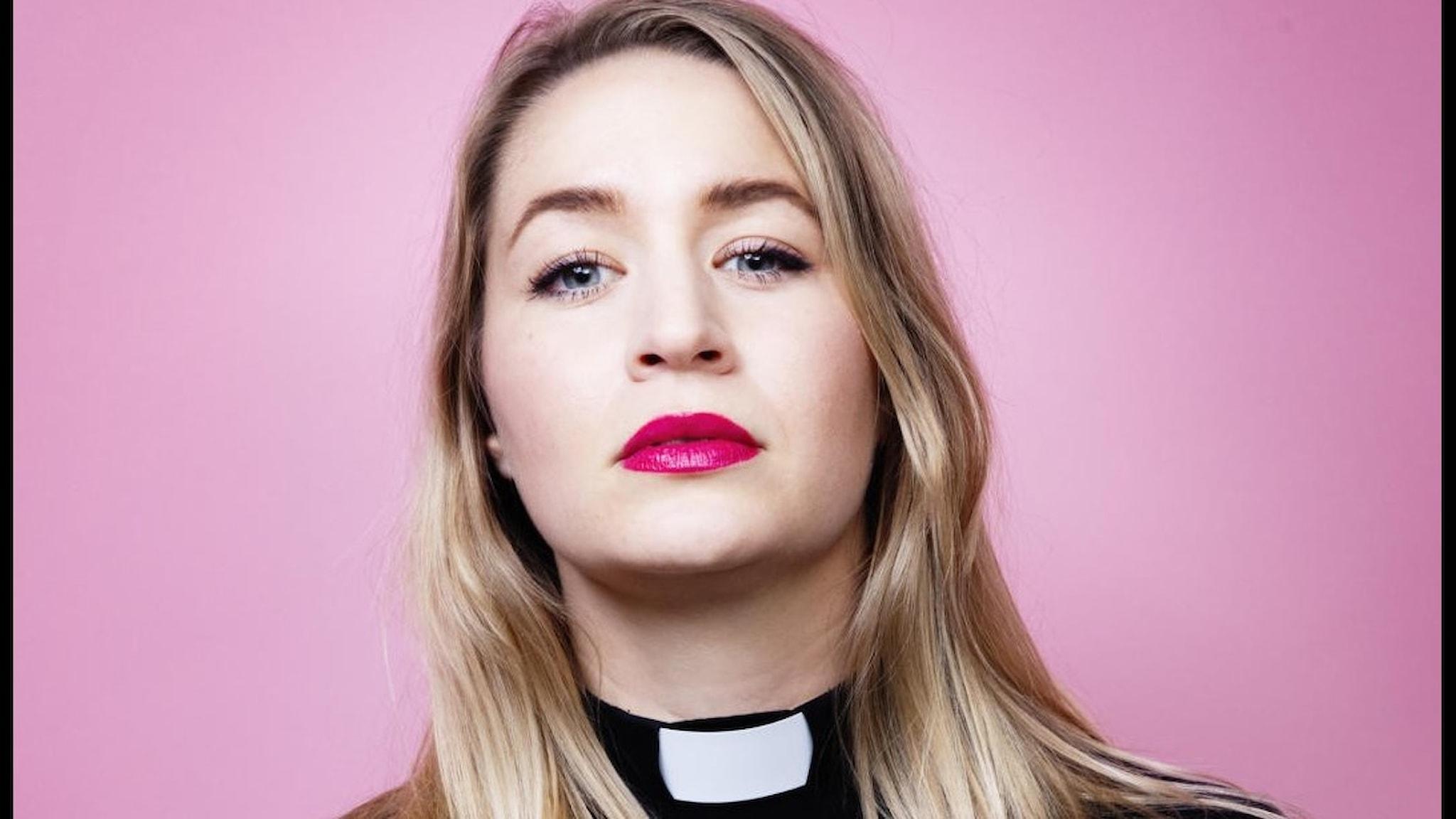 En ung kvinnlig blond pastor med prästkrage mot rosa bakgrund