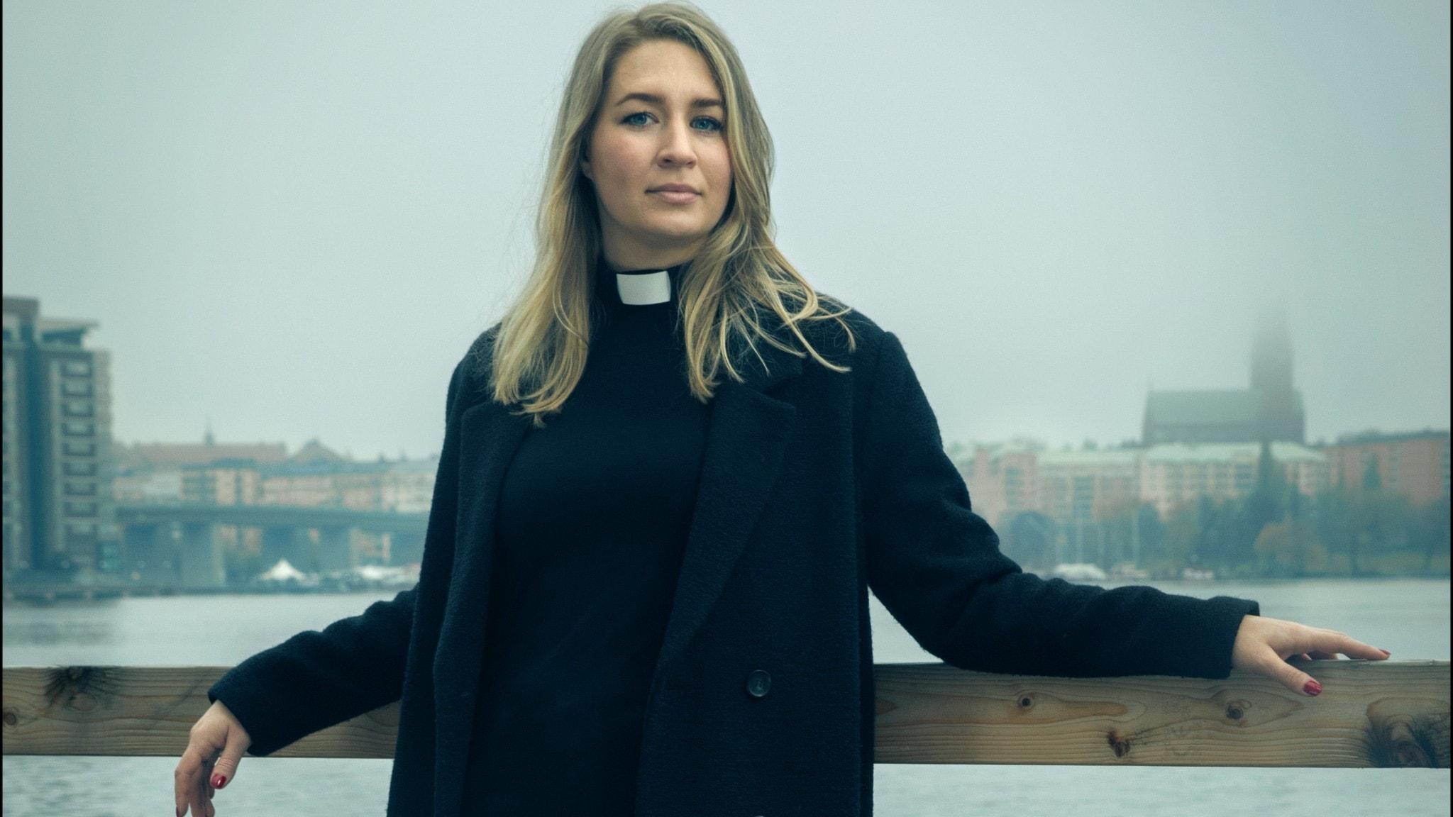 En ung kvinnlig pastor i prästkläder står på en bro med en stad i bakgrunden