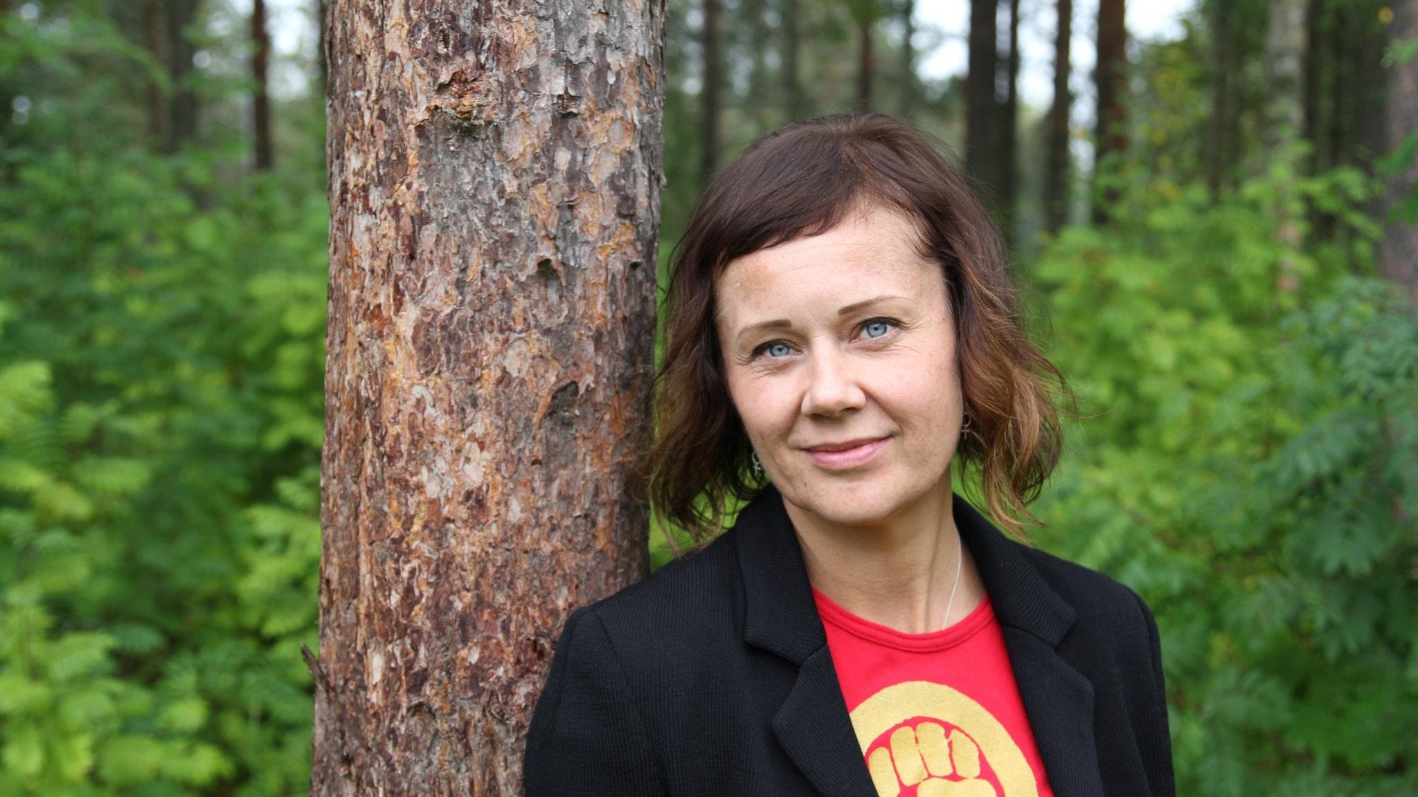 Kvinna i svart kavaj som lutar sig mot en trädstam.