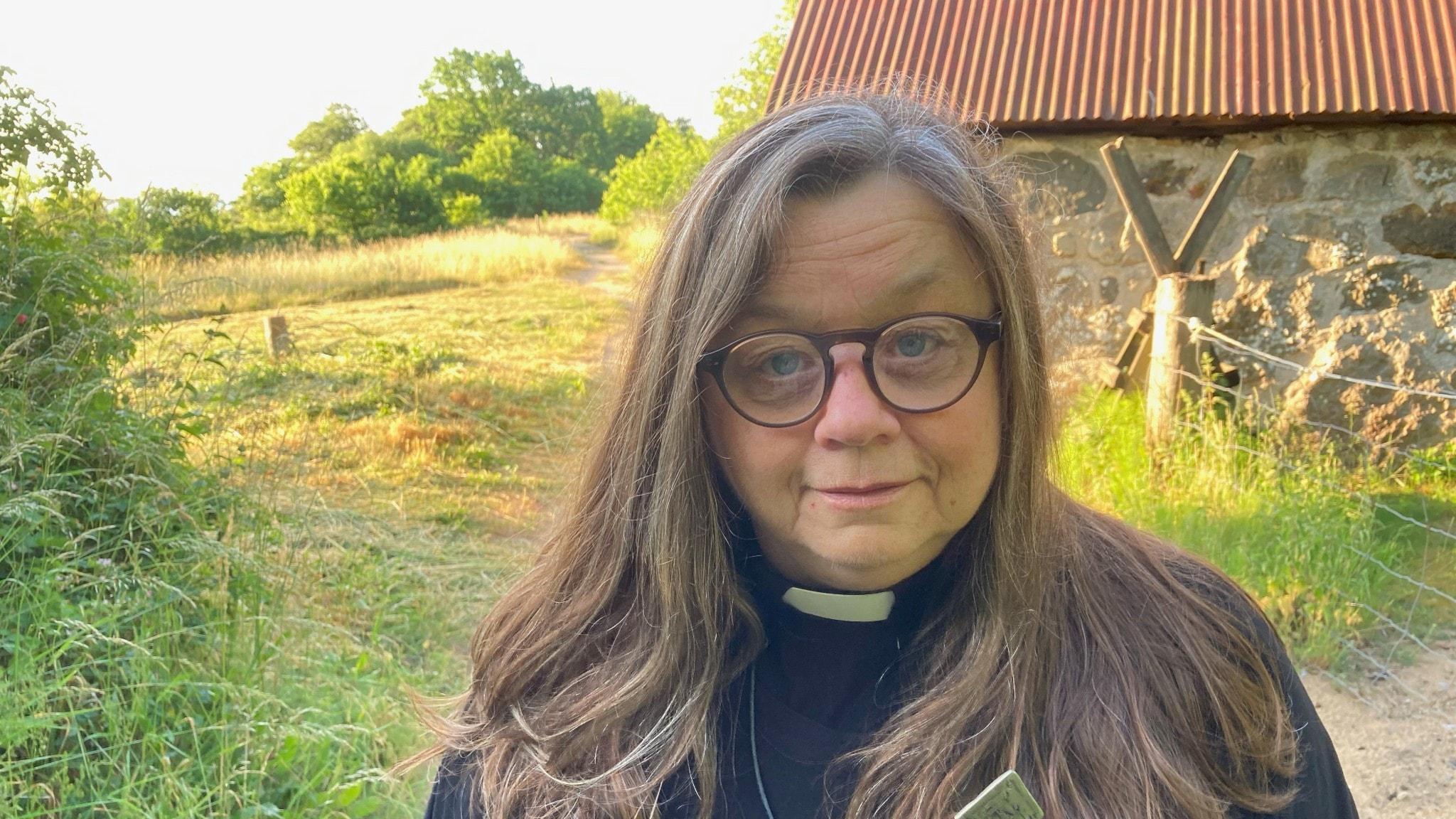 En kvinnlig präst framför ett litet stenhus